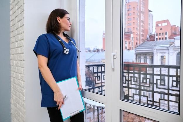 Vrouwelijke verpleegster met medisch dossier dat op kantoor staat en uit het raam kijkt, vrouwelijke huisarts, kopieer ruimte
