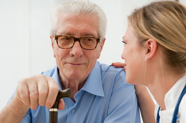 Vrouwelijke verpleegster praten anda het verzorgen van senior oude man in het ziekenhuis