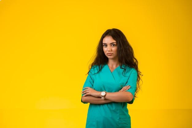 Vrouwelijke verpleegster sluitende handen en ziet er twijfelachtig uit.