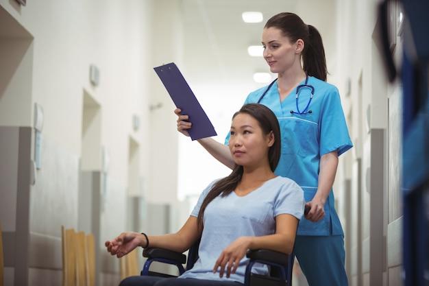 Vrouwelijke verpleegsters bijwonende patiënt op rolstoel in gang