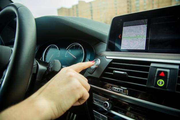Vrouwelijke vinger drukt op de start-stop-motorknop op autodashboard close-up auto-interieur details