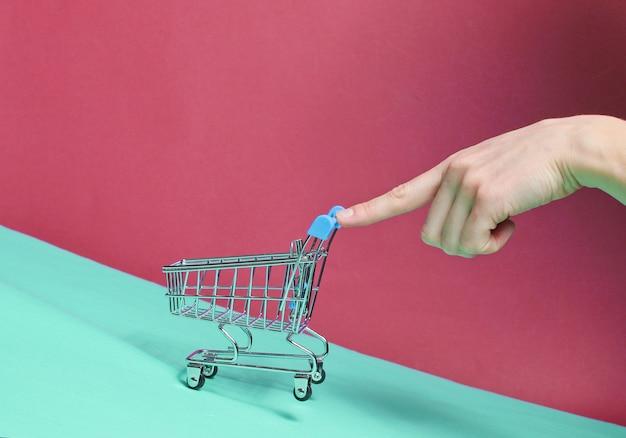 Vrouwelijke vinger duwt schuin leeg mini winkelwagentje omhoog. winkelen concept, levering