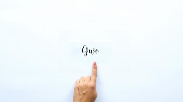Vrouwelijke vinger weergegeven op een notitie met een woord geven