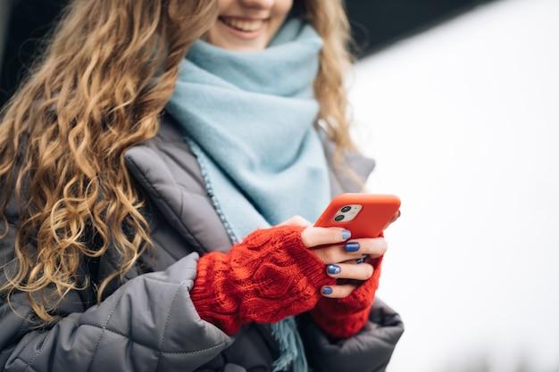 Vrouwelijke vingers die buitenshuis op mobiel tikken.