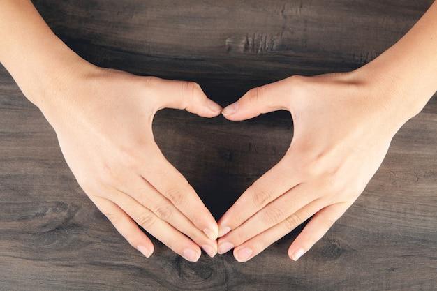 Vrouwelijke vingers tonen een hart op tafel
