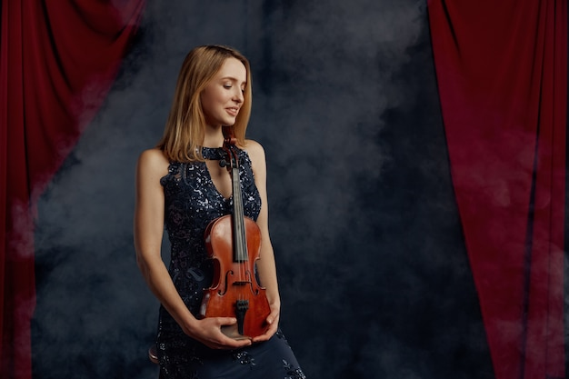 Vrouwelijke violist houdt viool in retro stijl. vrouw met muzikale snaarinstrument, muziekkunst, musicusspel op altviool