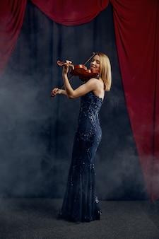 Vrouwelijke violist met boog en viool, soloconcert op het podium. vrouw met muzikale snaarinstrument, musicusspel op altviool