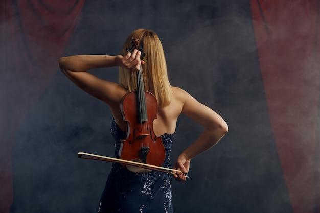 Vrouwelijke violiste met strijkstok en viool achter haar rug, virtuoos optreden op het podium. vrouw met muzikale snaarinstrument, muziekkunst, musicusspel op altviool