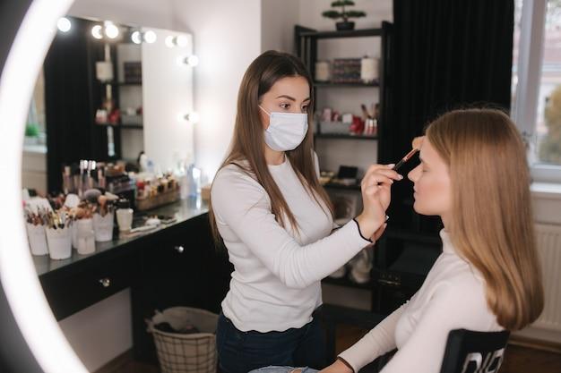 Vrouwelijke visagist die in de schoonheidssalon werkt tijdens quarantaine