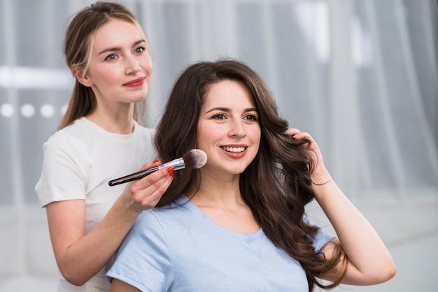 Vrouwelijke visagiste die make-up doet