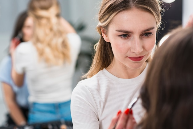 Vrouwelijke visagiste die make-up op cliënt zet