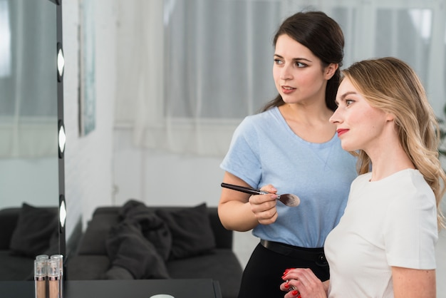 Vrouwelijke visagiste met cliënt die in spiegel kijkt