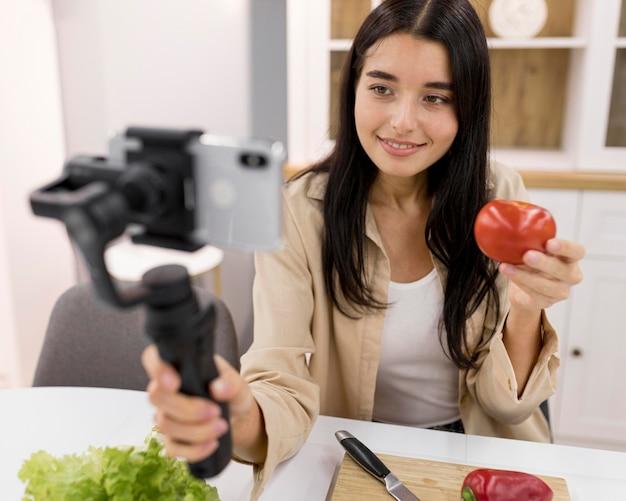 Vrouwelijke vlogger die thuis video opneemt