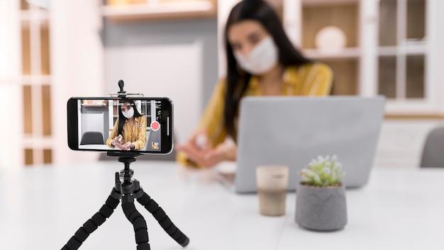 Vrouwelijke vlogger thuis met laptop en smartphone
