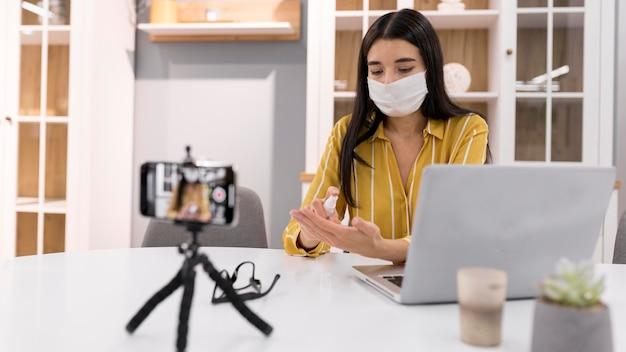 Vrouwelijke vlogger thuis met medisch masker en smartphone