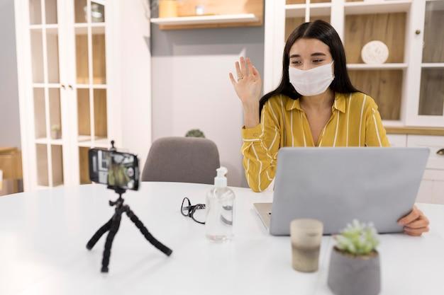 Vrouwelijke vlogger thuis met smartphone en medisch masker