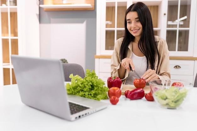 Vrouwelijke vlogger thuis video opnemen met laptop