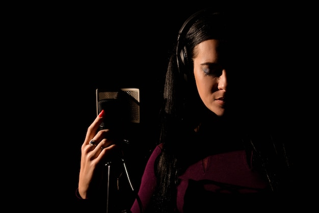 Vrouwelijke vocale artiest zingt in een opnamestudio.