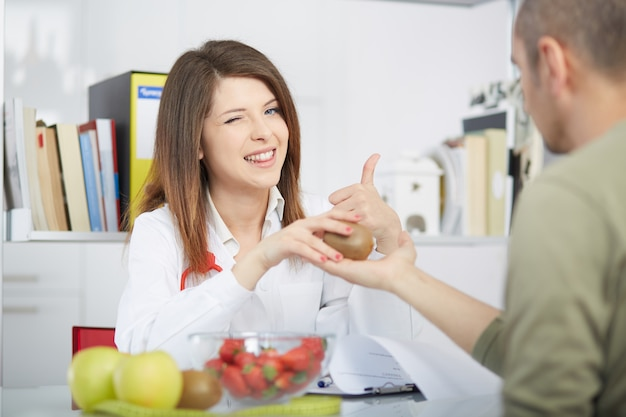 Vrouwelijke voedingsdeskundige die in haar studio werkt