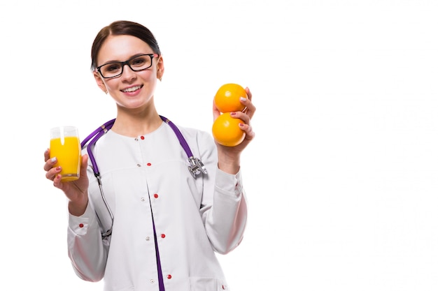 Vrouwelijke voedingsdeskundige houdt sinaasappels en glas vers sap in haar handen
