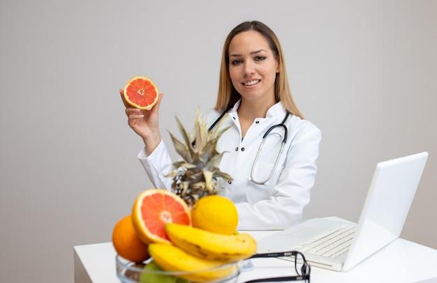 Vrouwelijke voedingsdeskundige met vruchten die bij haar bureau werken