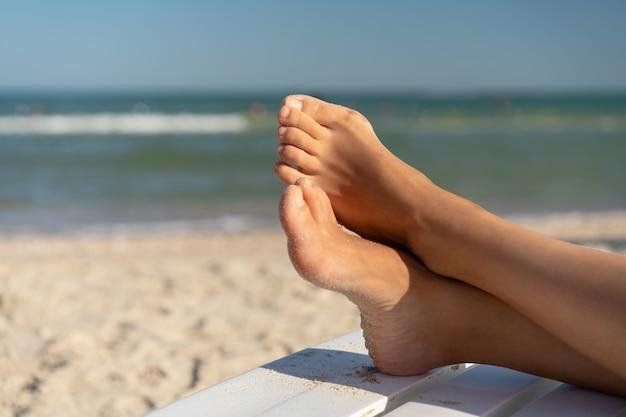 Vrouwelijke voet met halluxvalgus op het strand op de dag van de vakantiezomer