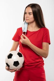 Vrouwelijke voetballer met de bal van de maskerholding