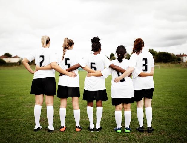 Vrouwelijke voetballers die bij elkaar kruipen en samen staan