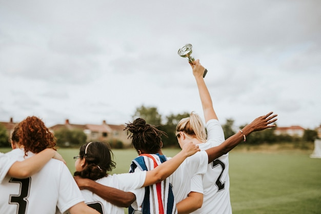 Vrouwelijke voetballers die een winnende kop thuis nemen