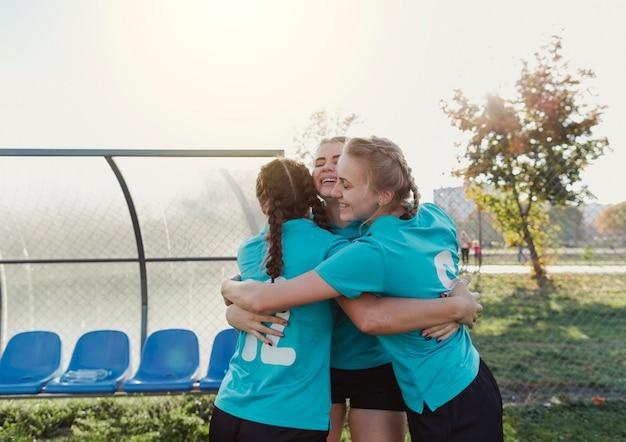 Vrouwelijke voetballers omhelzen elkaar