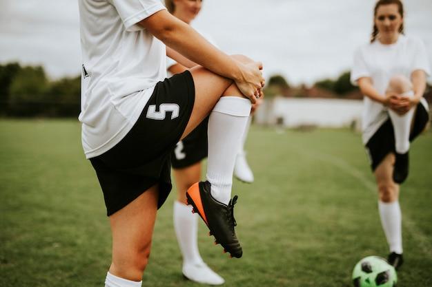 Vrouwelijke voetbalteam spelers die pre-spel uitrekken