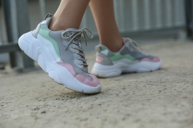 Vrouwelijke voeten die sportschoenen buitenshuis dragen