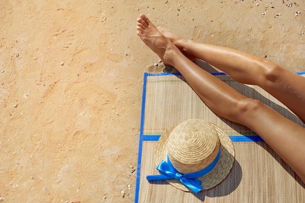 Vrouwelijke voeten en een strooien hoed tegen de zee op het strand van de zomer