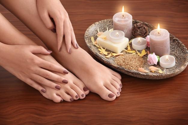 Vrouwelijke voeten en handen met bruine manicure en kuuroordsamenstelling op houten