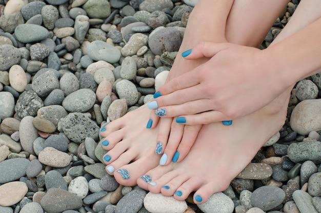 Vrouwelijke voeten en handen met een blauwe manicure op kiezelstenen