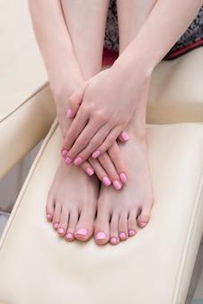 Vrouwelijke voeten en handen met een roze manicure. schoonheidssalon. detailopname