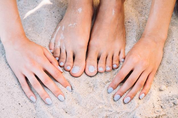 Vrouwelijke voeten en handen met manicure in het zand van het de zomerstrand