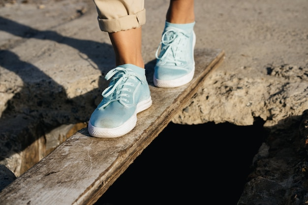 Vrouwelijke voeten in beige broek en sneakers zijn op het bord over de afgrond