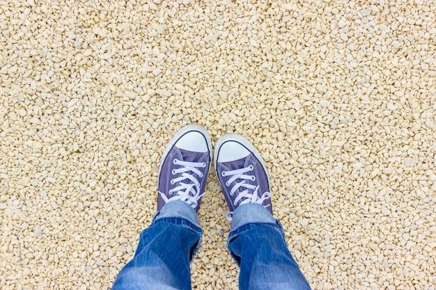 Vrouwelijke voeten in blauwe sneakers op een licht kiezelstrand
