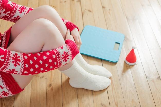 Vrouwelijke voeten in de buurt van blauwe elektronische weegschaal voor gewichtsbeheersing met kerstmuts op houten vloer