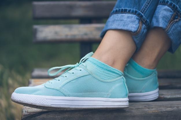 Vrouwelijke voeten in jeans en sportschoenen