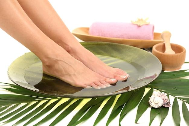 Vrouwelijke voeten in kuuroordkom met water, dat op witte oppervlakte wordt geïsoleerd