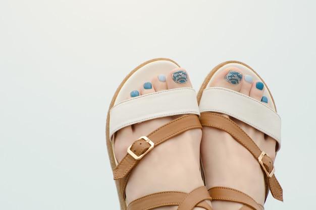 Vrouwelijke voeten in sandalen met een manicure