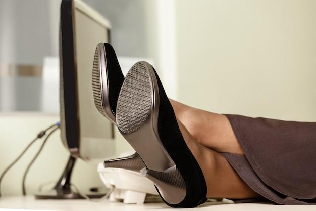 Vrouwelijke voeten in schoenen op een bureau