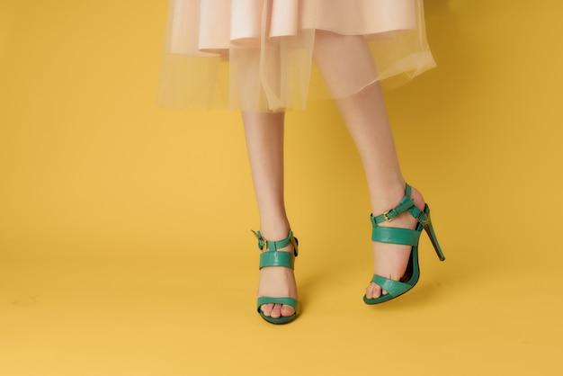 Vrouwelijke voeten in schoenen zomer zomer stijl gele achtergrond mode. hoge kwaliteit foto