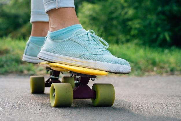 Vrouwelijke voeten in sneakers op een gele skateboardclose-up