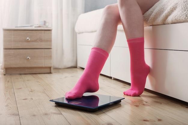 Vrouwelijke voeten in sokken op de vloerweegschaal