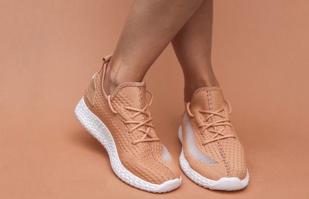 Vrouwelijke voeten in trendy sportschoenen op bruine achtergrond
