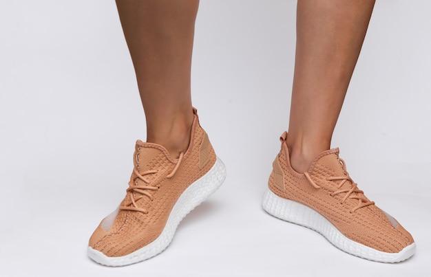 Vrouwelijke voeten in trendy sportschoenen op witte achtergrond
