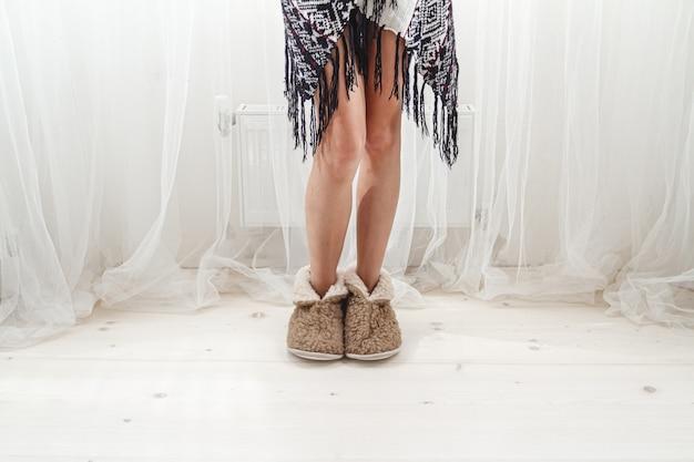 Vrouwelijke voeten in warme knusse pantoffels thuis